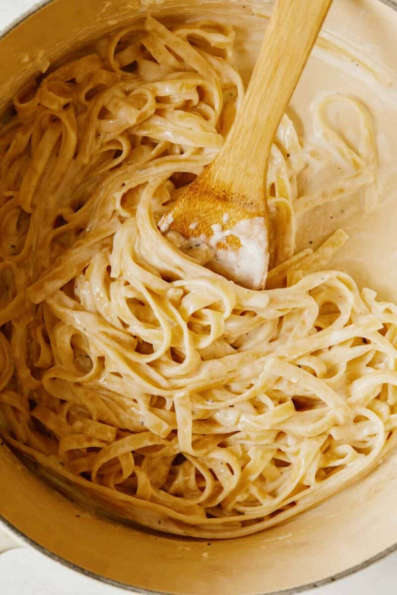 Close up of fettuccine alfredo with a wooden spoon.