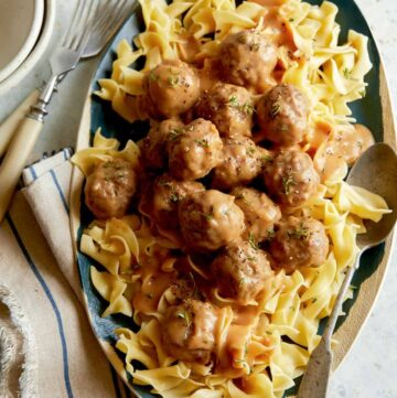 Grass fed lamb meatballs with gravy over egg noodles with forks.