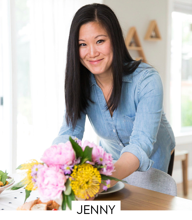 A beautiful smiling woman leaning over a table with flowers.