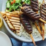 :amb Kofta with rice and lettuce on a platter.