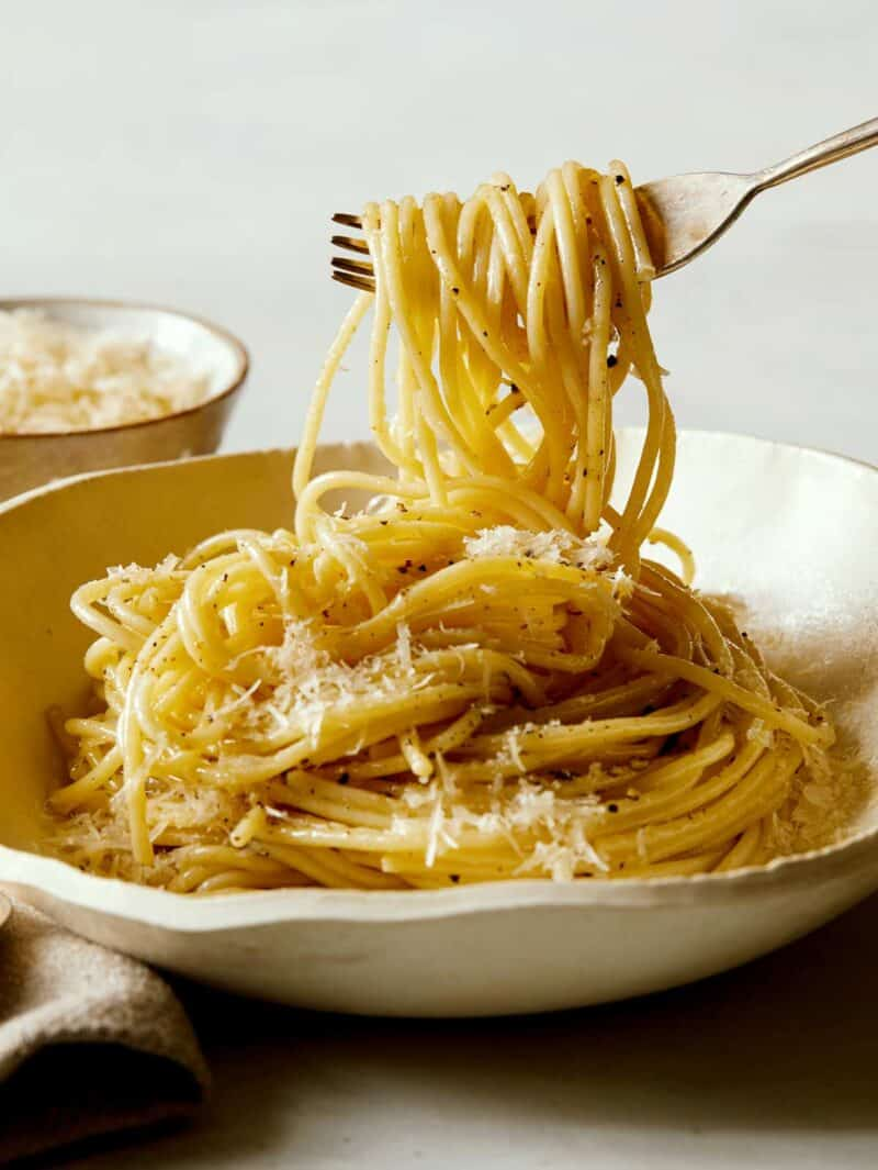 forkful of cacio e pepe being lifted from plate with small ramekin of grated parmesan in the back