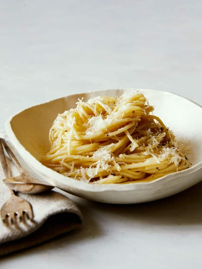 Bowl of Cacio e Pepe with a fork and spoon.