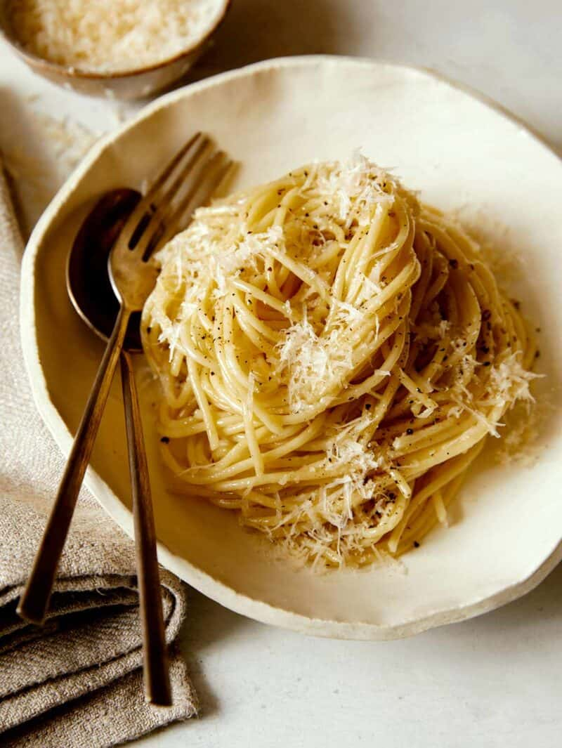 finished plate of cacio e pepe with fork and spoon and ramekin of grated parmesan in background