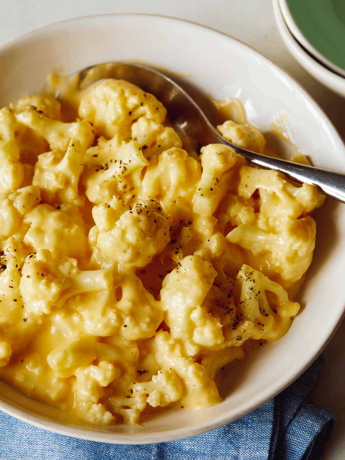 Creamy Cauliflower Mac and Cheese in a bowl with a spoon it and some bowls on the side.