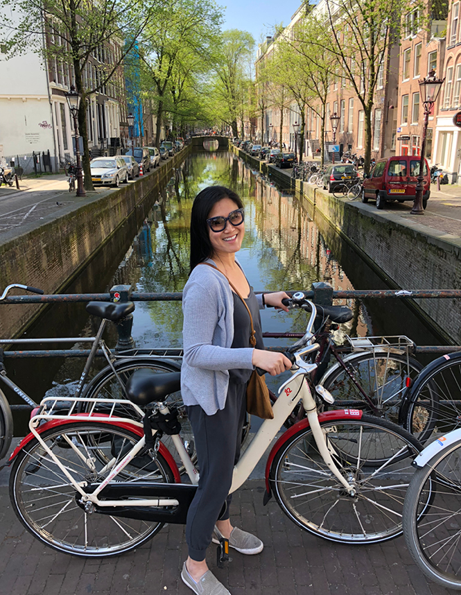 A lovely woman standing on a bicycle in front of a city canal.