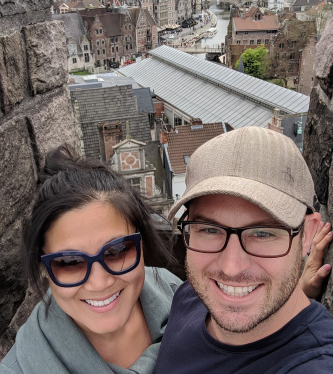 A selfie of a happy couple with buildings in the background.