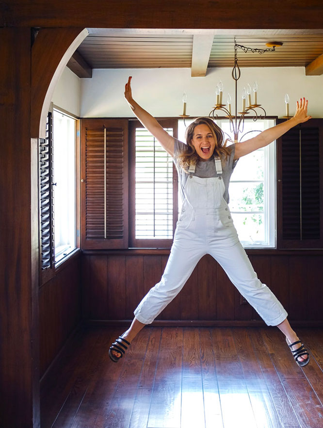 An excited woman jumping up with arms and legs starfished in a living room.