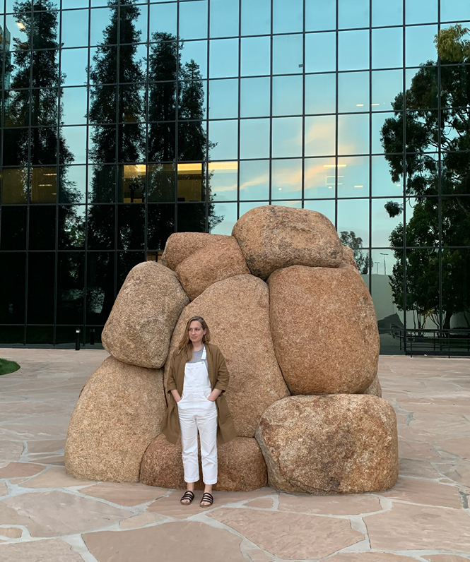 A relaxed woman standing in front of a stone sculpture with a building in the background.