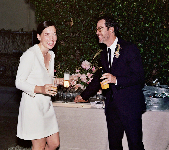 An ecstatic newly married couple with a champagne bottle and glasses.