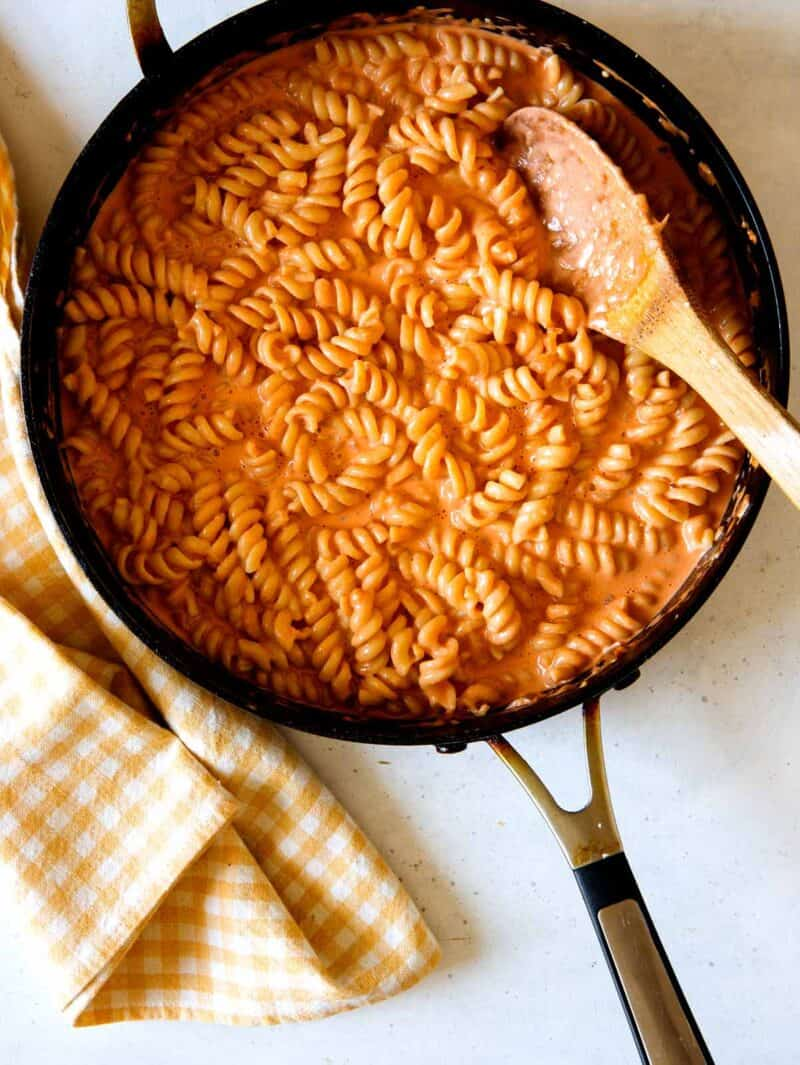 skillet of rotini tossed in vodka sauce with wooden spoon nestled into pasta