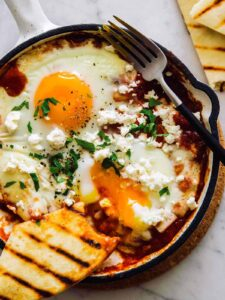 An individual shakshuka with hominy and feta and a fork.