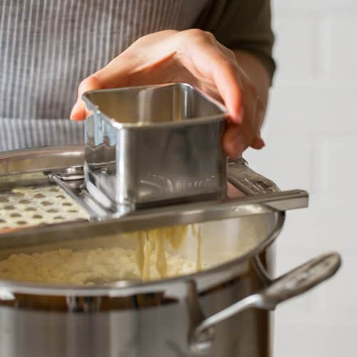 A person making spaetzle over a pot.