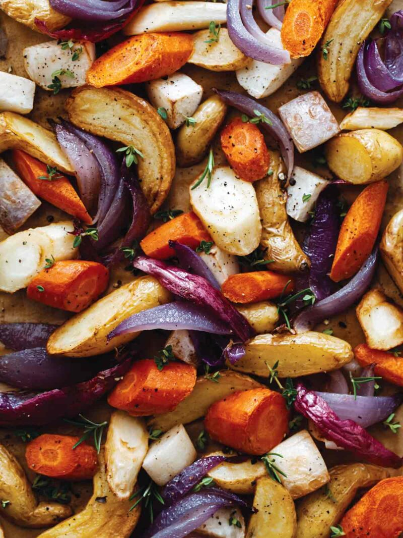 A close up of a variety of aromatic roasted root vegetables.