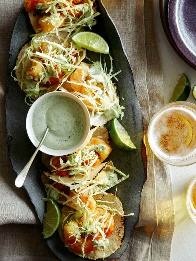 Beer Battered Shrimp Tacos on a platter with beer nearby.
