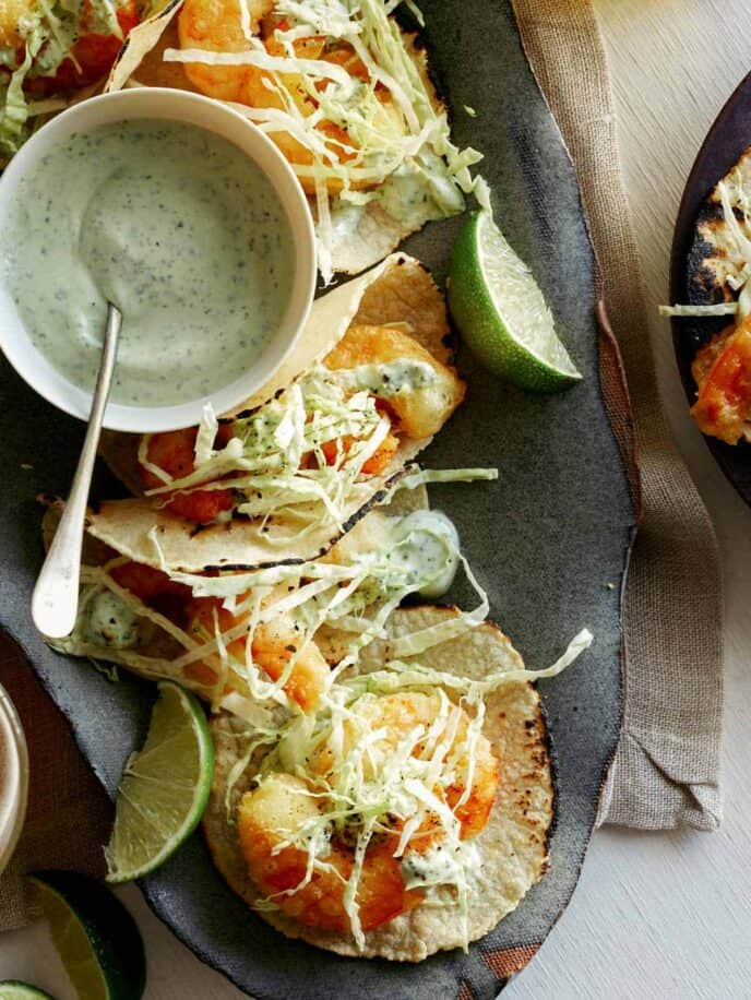 Beer battered shrimp tacos with lime wedges and a side of cilantro lime crema.