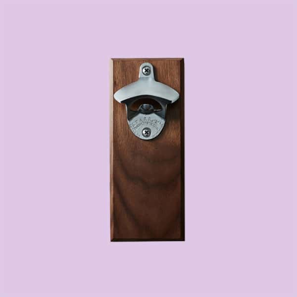 A magnetic bottle opener on a piece of wood, on a light purple background.