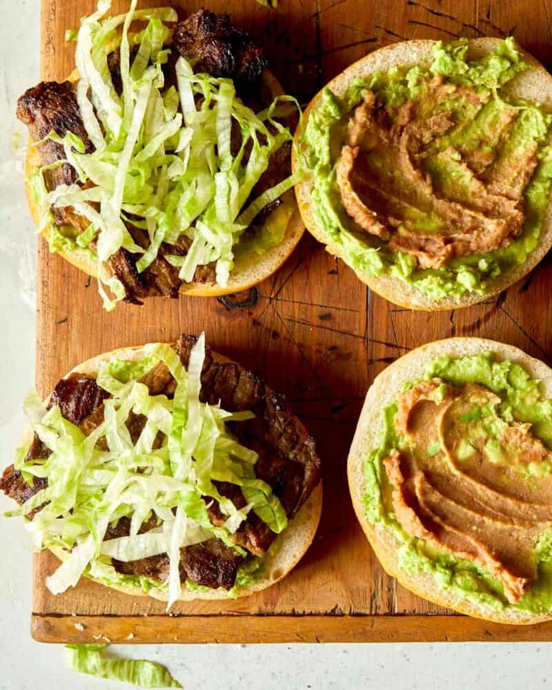 The making of a carne asada sandwich over head with shredded lettuce