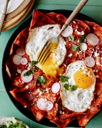 A recipe for easy Chilaquiles with a fork that has broken an egg yolk.