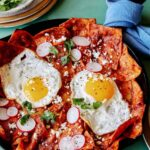 Chilaquiles in a skillet with plates next to it.
