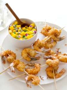 A bowl of mango salsa with a wooden spoon on a plate of coconut shrimp skewers.