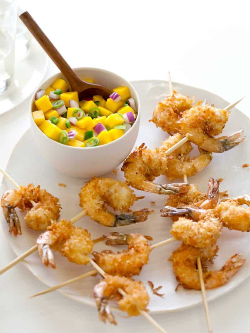 A bowl of mango salsa with a wooden spoon on a plate with coconut shrimp skewers.