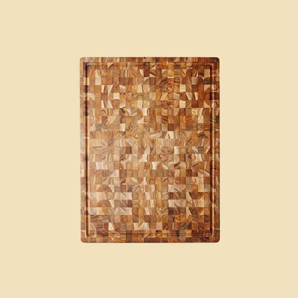 A cutting board made of teak wood with an interesting design on a yellow background.