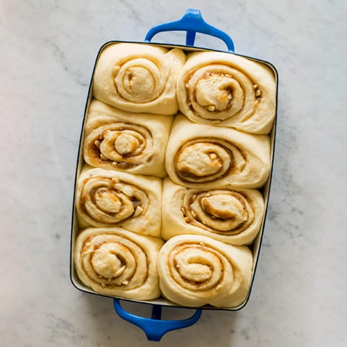 Blue rectangular pan of raw cinnamon rolls.