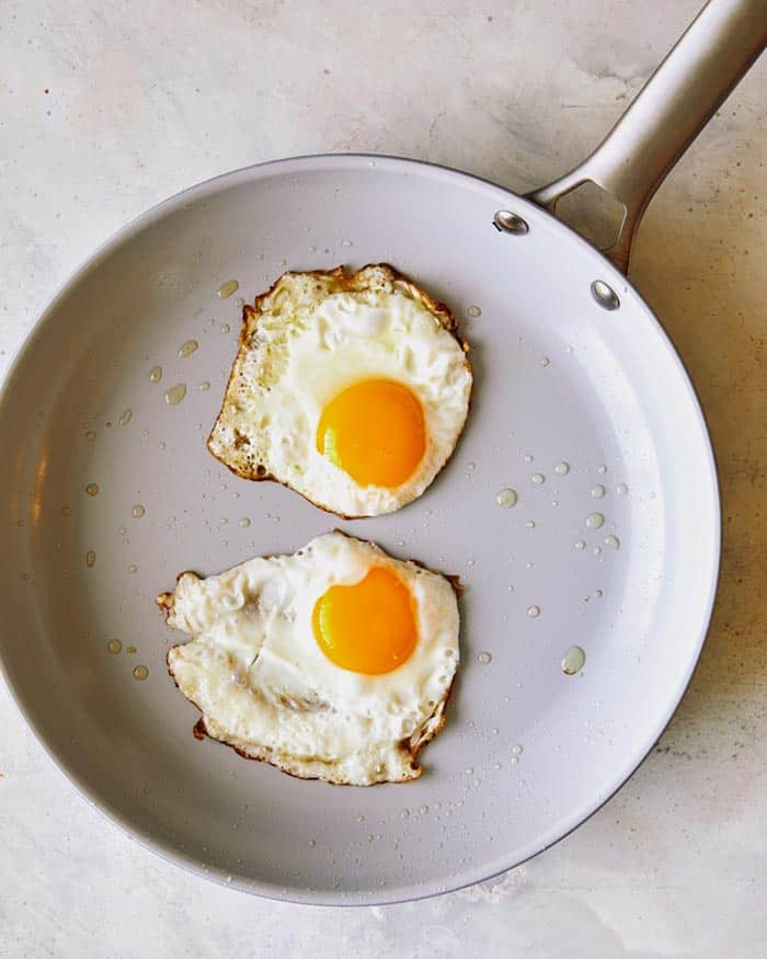 Freshly fried eggs in a non stick skillet showing the crispy edges of the eggs.