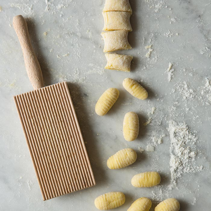 Raw gnocchi cut next to a gnocchi paddle.