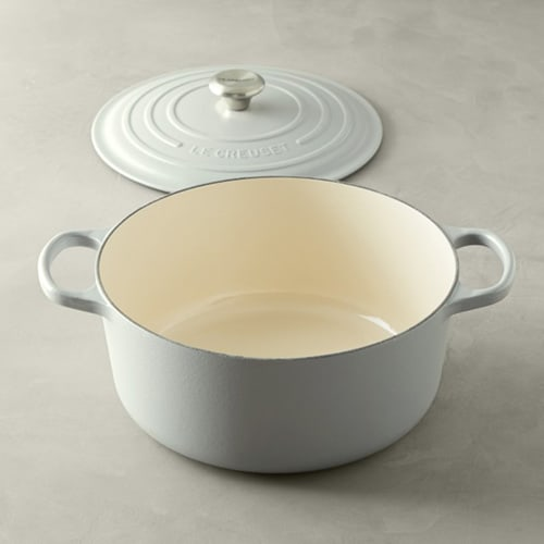 White Le Creuset Signature Round Cast Iron Dutch Oven with lid to the side.