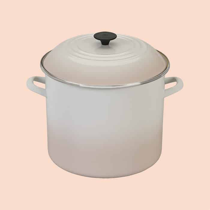 White Le Creuset stockpot with lid on.