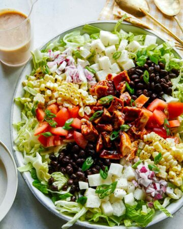 Loaded BBQ chicken salad on a plate with dressing on the side.