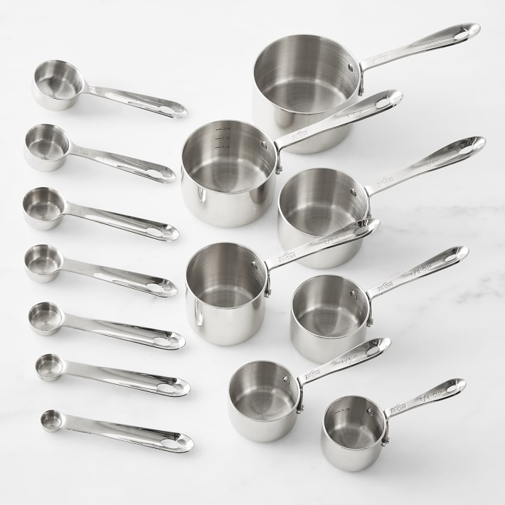 Set of measuring spoons and measuring cups laid out vertically from largest to smallest.