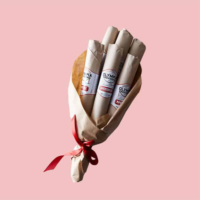A bouquet of 6 salamis to be given as a gift on a solid pink background.
