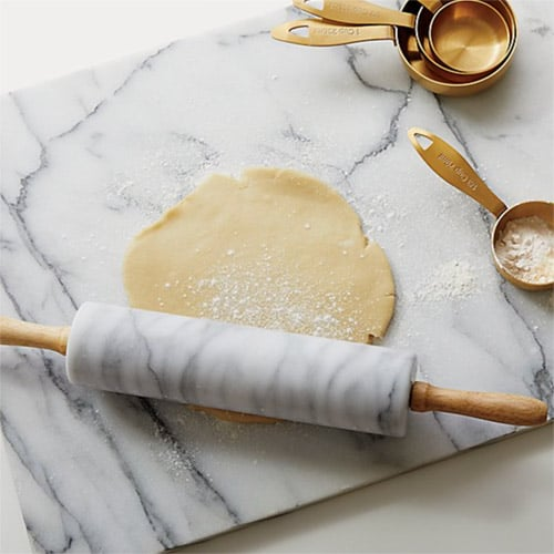 Marble cutting board and rolling pin, rolling out dough with measuring cups nearby.