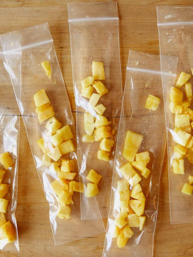 Pineapple chunks in ice pops sleeves ready for filling.