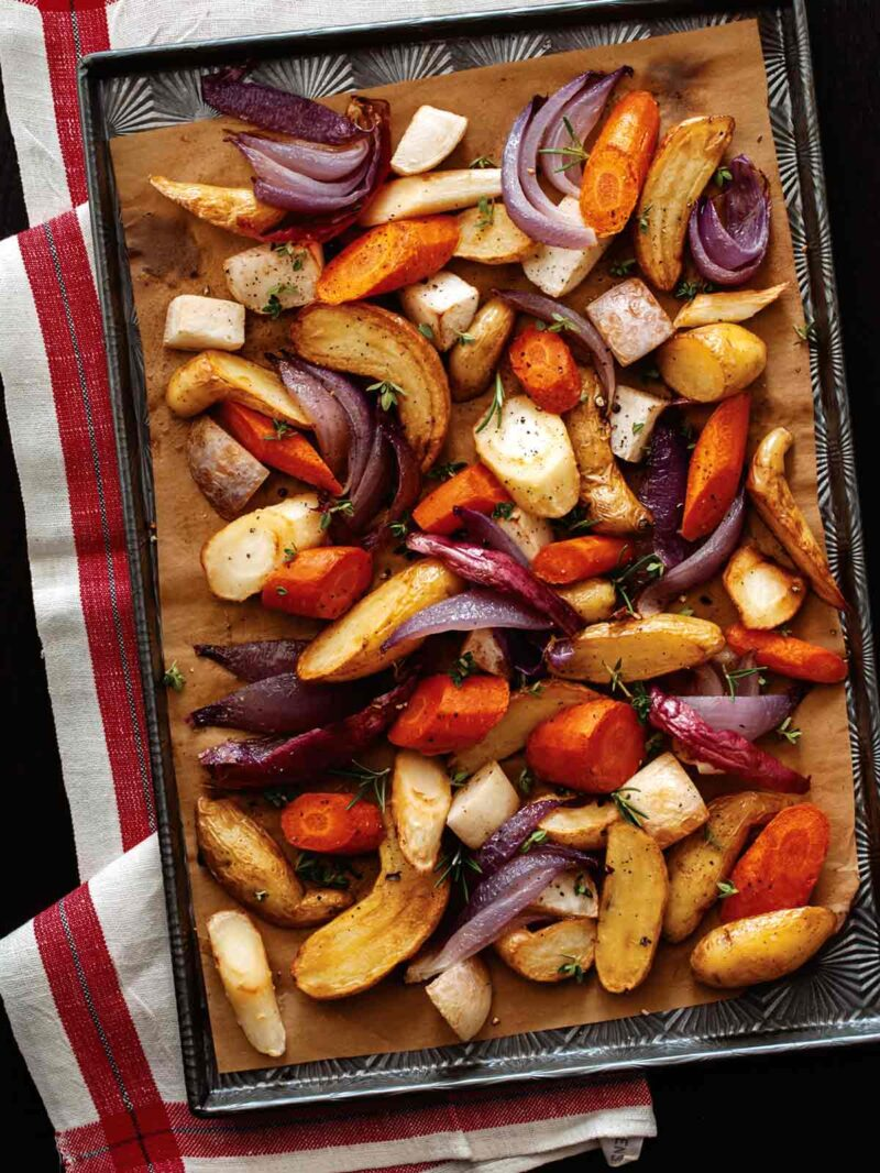 Aromatic roasted root vegetables on a sheet pan, overhead.