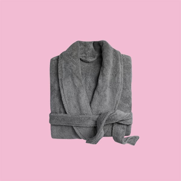 A classic plush bathrobe on a pink background.