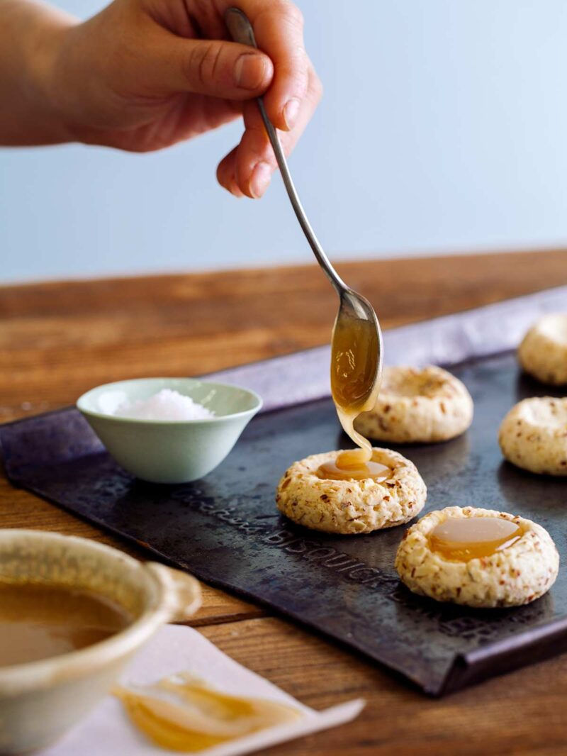 Filling the center of almond thumbprint cookies with caramel.