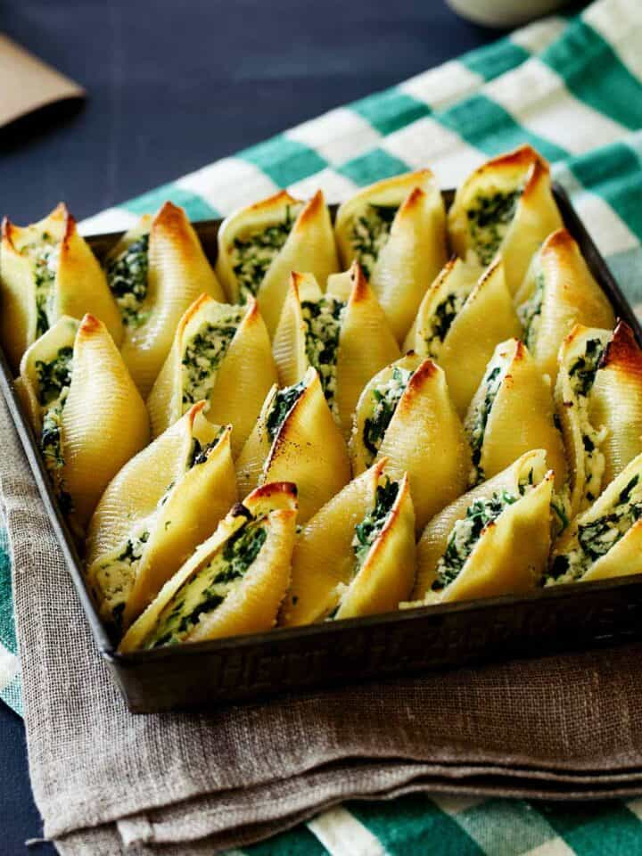 A close up of a pan full of spinach ricotta stuffed shells.