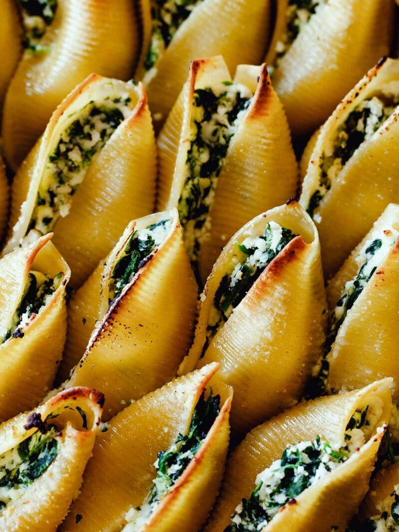A close up image of Spinach and Ricotta Stuffed shells showing the filling in the pasta.