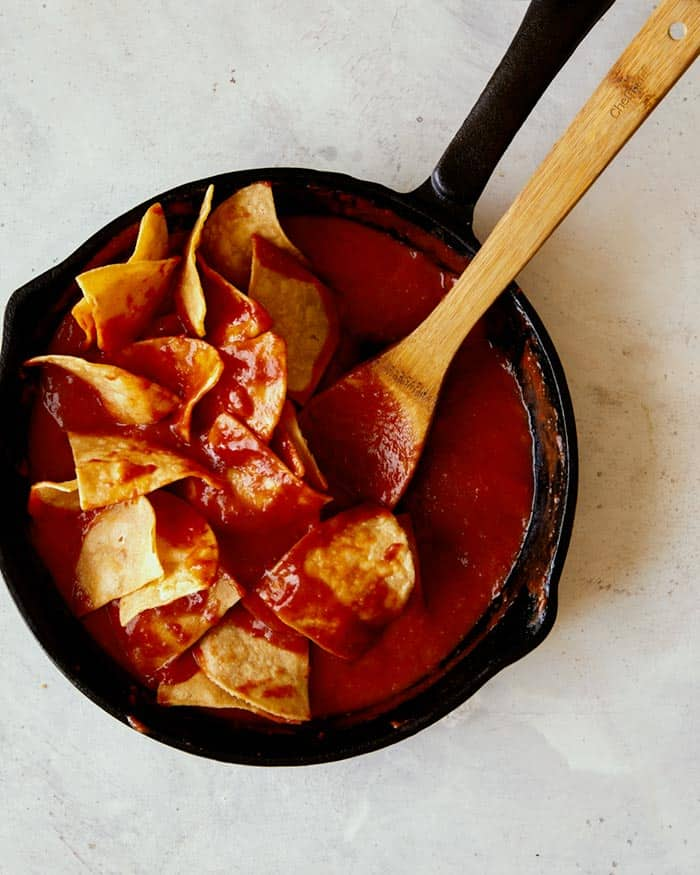 Tortilla chips in a skillet being gently folded together with a red sauce to make chilaquiles.