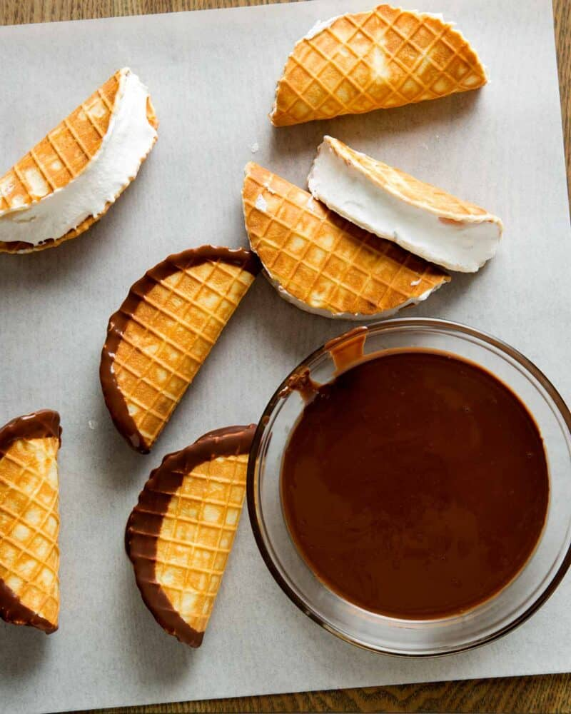 Mini Choco Tacos filled with ice cream and them dipped in a bowl of chocolate and layed out to dry.