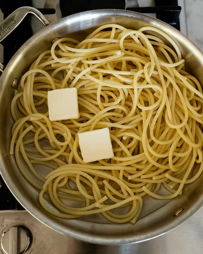 Cooked bucatini noodles in a skillet with pads of butter.