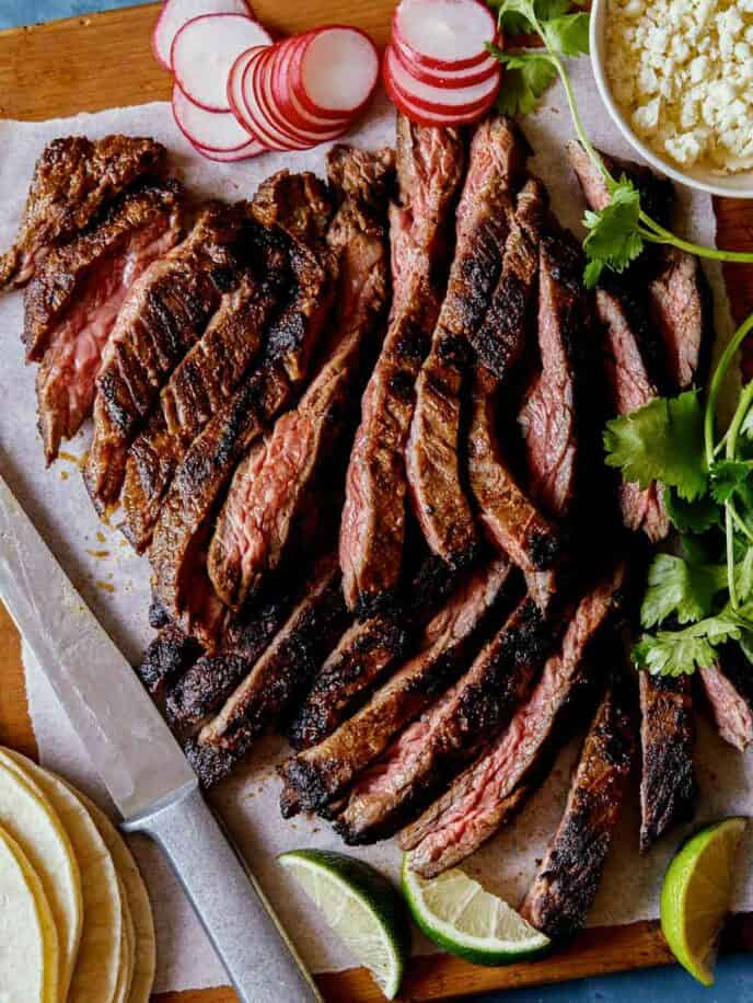 Sliced carne asada with a knife, tortillas, cilantro and radishes.