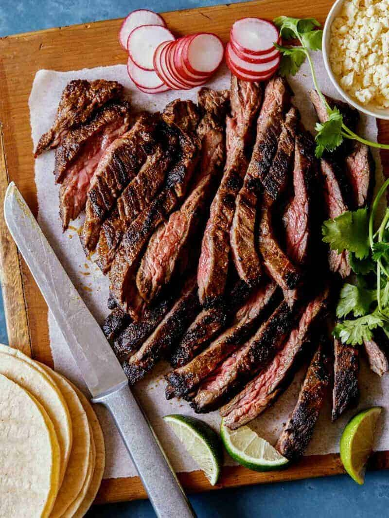 Freshly grilled and sliced Carne Asada on a cutting board with some taco fixings around it.