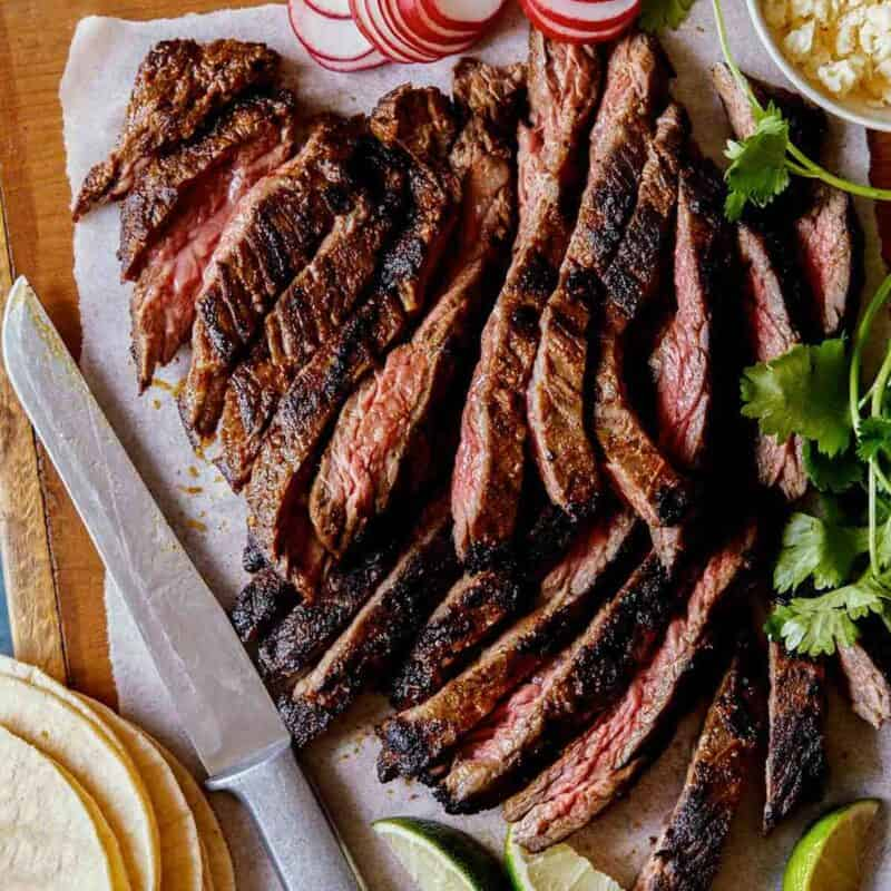Carne Asada recipe on a cutting board with ingredients on the side.