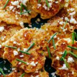 Corn Cakes close up on a platter with cheese and chives.