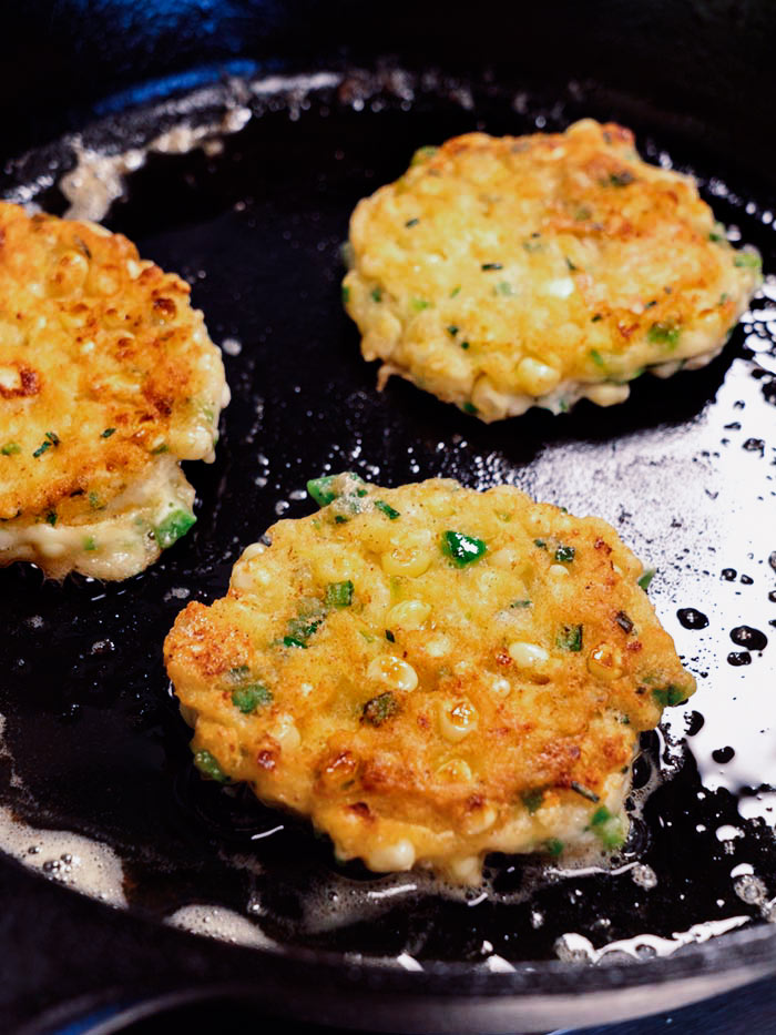 Corn cakes in a skillet after being flipped.