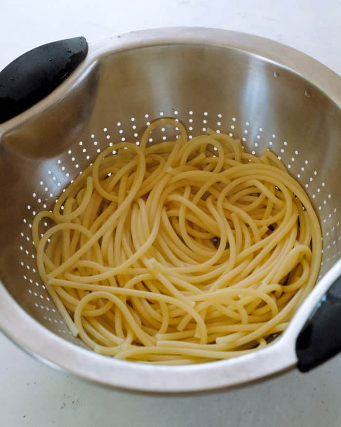 Cooked bucatini noodles in a strainer.